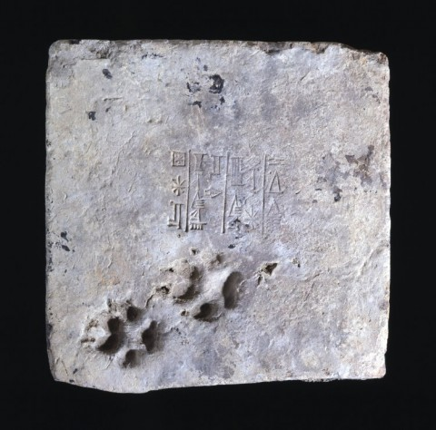 Brick from the ziggurat of Ur, stamped with Ur-Nammu's name, c. 2100 BCE. Two dog's paw marks are seemingly-accidentally marked on one side. Image courtesy British Museum.