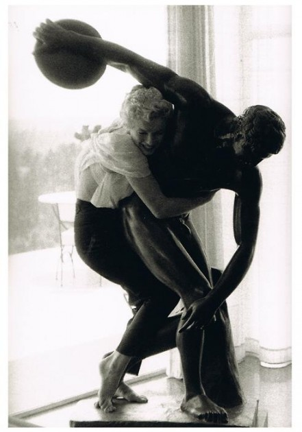 "Marilyn Monroe posing with hairdresser Sidney Guilaroff's statue of the Discobolus (""Discus Thrower""). Photo by Milton Greene, 1956"