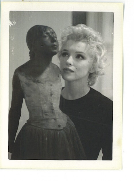 "Marilyn Monroe looking at a statue of Edgar Degas' ""Little Dancer of Fourteen Years."" Photo taken at William Goetz's house, 1956"